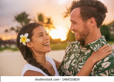 Happy couple lovers in love on romantic sunset beach vacation in Hawaii travel. Asian woman hugging Caucasian man smiling, interracial relationship. Newlyweds honeymoon or wedding on Tahiti beach.