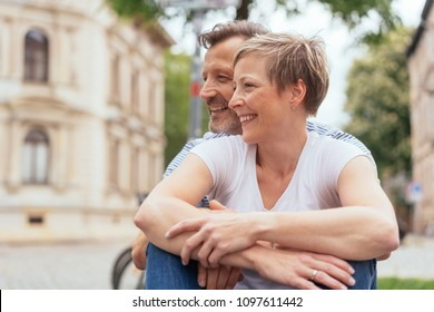 Happy couple in a loving embrace outdoors in town looking to the side with beaming smiles watching