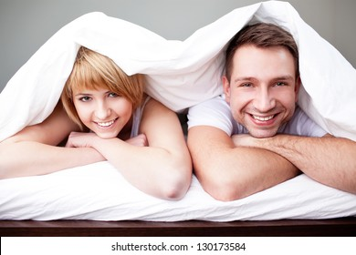 Happy couple lying in bed under the blanket