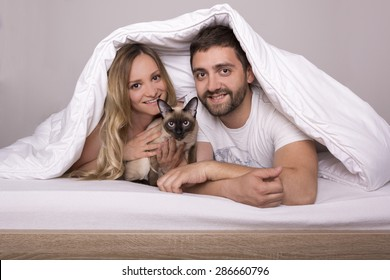 Happy couple lying in bed under the duvet with Siamese cat