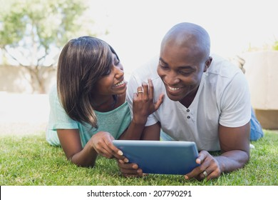 Happy couple lying in garden using tablet pc together on a sunny day