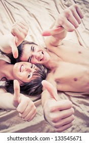 Happy couple lying on bed with thumbs up