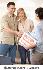 Happy couple making deal with estate agent, shaking hands.?