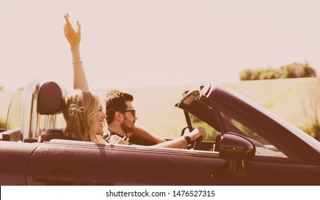 Happy couple making a tour in central italy. Driving on a convertible car in the italian countryside