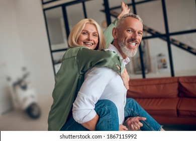 Happy couple. Man holding his wife on his back and both feeling awesome