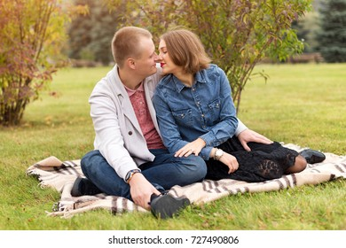 Happy couple, man and woman in autumn park sitting on a plaid. Beautiful smiling couple enjoying picnic day in the park. Love and tenderness, dating, romance. Lifestyle concept.