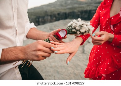 Happy couple of man and woman, guy made an offer and puts a wedding ring on the finger of a friend in a red dress on the nature near the fjords Trolltunga in Norway. Traveling in Europe, landscape.