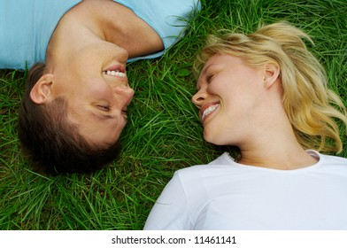 happy couple man and woman lie on green grass