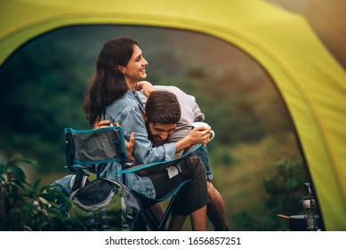 Happy couple man and woman sitting on chair in front of camping tent at campsite in the morning
