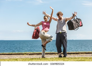 Happy couple man and woman with sport gym bags by sea ocean outdoor. Active young girl and guy in training suit sportswear raising hands up. Happiness.
