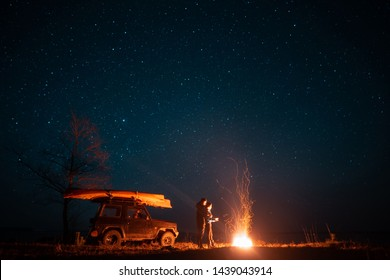 Happy couple man and woman standing in front burning bonfire