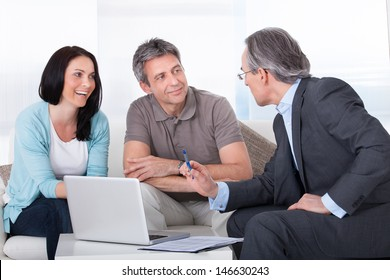 Happy Couple And Mature Consultant Discussing Together
