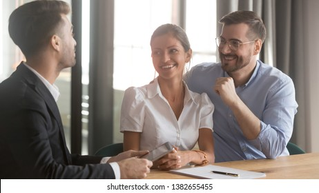 Happy couple meeting with realtor or real estate agent buying first shared home together, smiling millennial husband and wife excited to sign papers, discussing contract with banker or broker