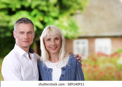 Happy couple middle age in front of a farmhouse