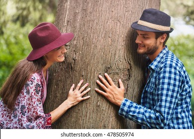 Happy couple in the middle age hug a tree. They wearing casual clothes and fashionable hats.