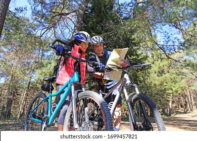 Happy couple mountain biking takes a look at the map