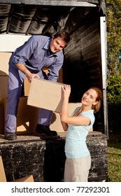 A happy couple moving boxes from a moving truck