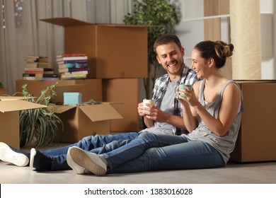 Happy couple moving home resting and talking sitting on the floor drinking coffee
