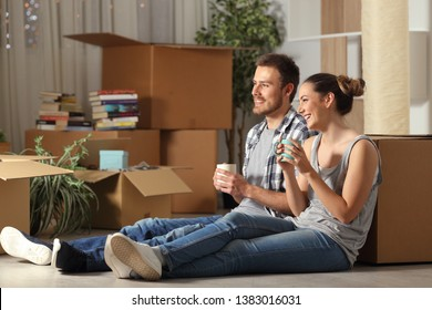 Happy couple moving home resting sitting on the floor contemplating house