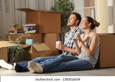 Happy couple moving home resting breathing fresh air sitting on the floor holding coffee cups
