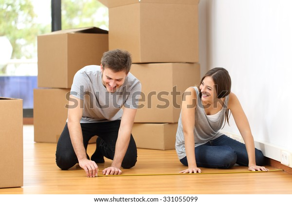 Happy couple moving house and taking measure together for the furniture