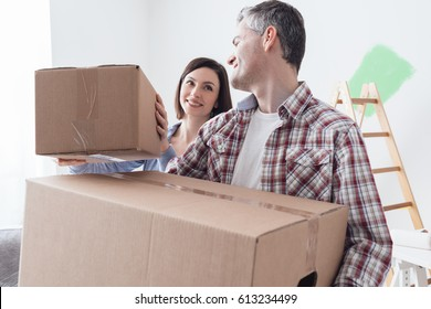 Happy couple moving into a new house and doing home renovations, they are carrying cardboard boxes