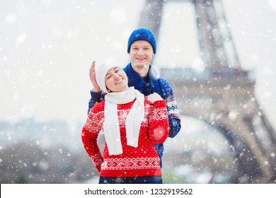 Happy couple near the Eiffel tower on a winter day under the falling snow. Trip to Paris during season holidays