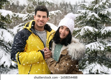 Happy couple near snowy fir trees outdoors. Winter vacation