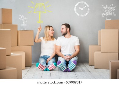 Happy couple at new home. Man and woman having fun together. Moving house day and interior renovation concept
