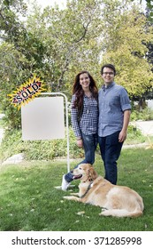 happy couple as new homeowners with dog in front of first home