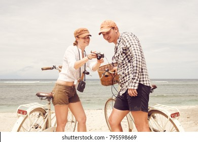 Happy couple with old fashioned bicycles looks at the pictures on the beach. Enjoy each other's company on vacation.