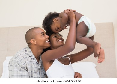Happy couple on bed with baby daughter at home in the bedroom