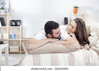 Happy couple on bed sofa in living room