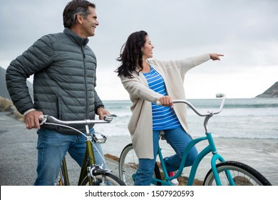 Happy couple on bicycle pointing at distance on beach during winter