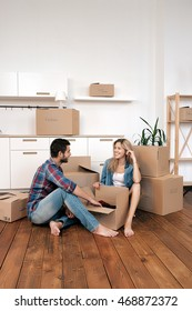 Happy couple on floor moving in new home.Copy space.