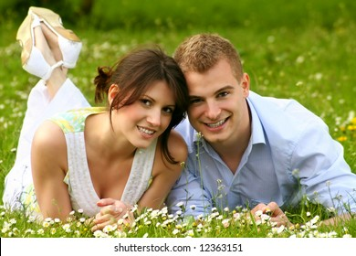a happy couple on a green meadow is smiling