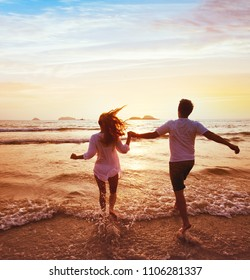 happy couple on honeymoon vacation travel, romantic dream beach holidays, happiness background, silhouettes of man and woman running to the sea at sunset together
