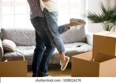 Happy couple on moving day concept, man lifting woman standing among cardboard boxes starting living together in new own house, husband holding embracing wife celebrating relocation, close up view