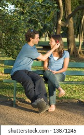 Happy couple on a park bench smile at each other as he places a red flower behind her ear. Vertically framed photograph.