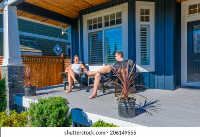 Happy couple on the porch of their house relaxing and enjoying sunny day. Vancouver, Canada.