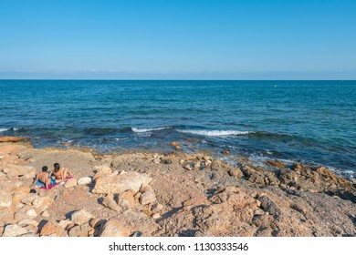 Happy couple on rocky beach Mediterranean sea Spain.