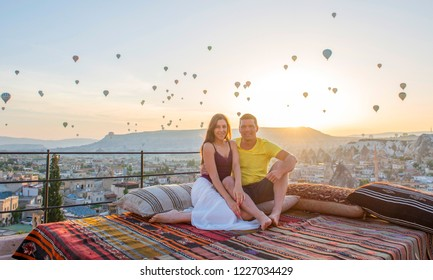 Happy couple on rooftop of an cave house during sunrise watching the hot air balloons of Kapadokya Cappadocia Turkey.