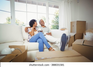 Happy couple on the sofa having coffee in their new house