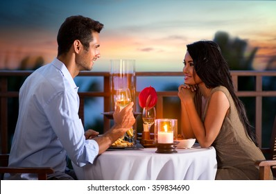 Happy couple on summer evening having romantic dinner outdoor