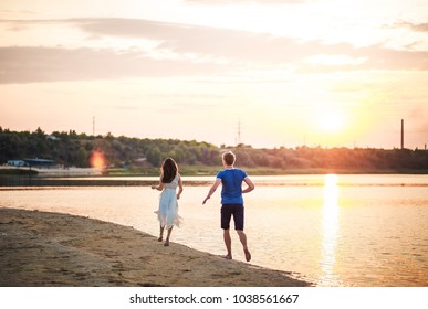 A happy couple on a sunset background running on the water. A man runs after a woman in a dress on a river, a lake, a pond, with splashes. Unplugged mindfull.