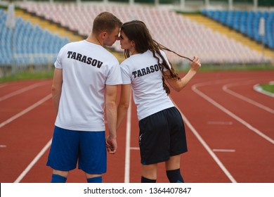 happy couple is on a treadmill at the stadium. man and woman after jog at the stadium. sports at the stadium outdoor. team on running on the track.love story concept.young loving couple playing sport