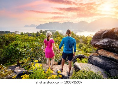 Happy couple on the tropical Phi Phi island at sunset in Southern Thailand. Travel magazine concept.