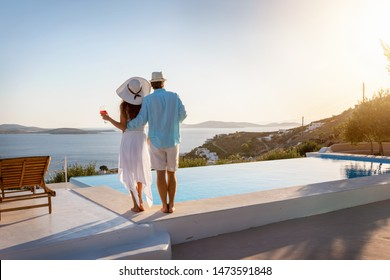 Happy couple on vacation time enjoys the summer sunset by the pool with an aperitif drink