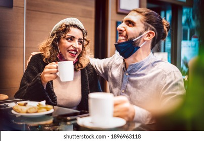 Happy couple with open mask having fun together at bar cafeteria - New normal lifestyle concept about young lovers on first date moment drinking american coffee - Warm filter with focus on woman face