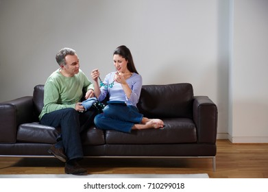 Happy couple opening presents on couch